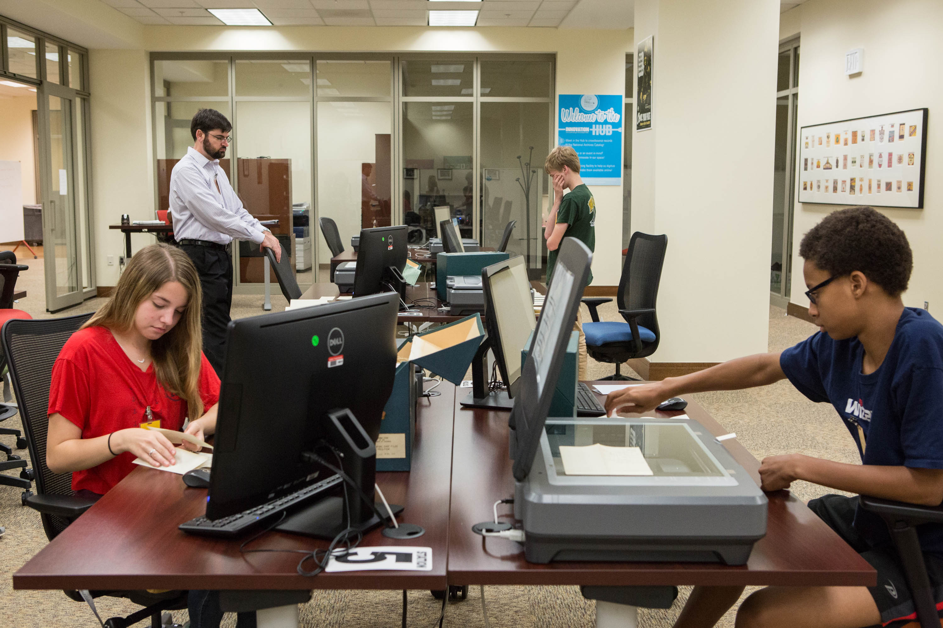 Three high school students and their THATclass leader, who volunteered to help with scanning in the digitization lab at the National Archives in Washington, DC, on July 20, 2016.