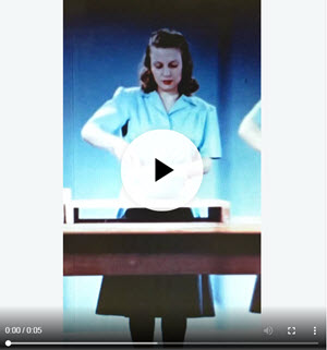 "Still from ""A Step Saving Kitchen,"" GIF, showing a woman stirring a bowl, with an overlaid play button and video status bar."